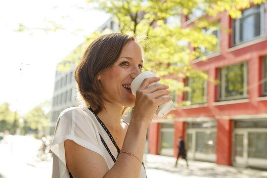Woman drinking a coffee to go, Munich, Bavaria, Germany
