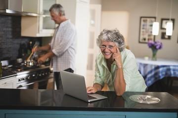 Smiling senior woman using laptop while husband cooking in
