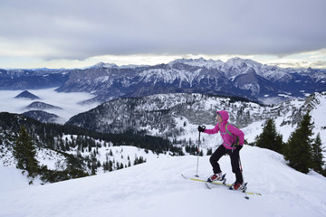 Female back-country skier ascending to Sonntagshorn, Berchtesgaden Alps in background, Chiemgau Alps, Salzburg, Austria