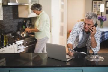 Senior man talking on phone while woman cooking in kitchen