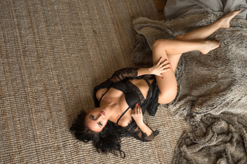 sexy woman in black lace lingerie lying on the floor and seductive posing. She tryes to seduce you. Temptation.