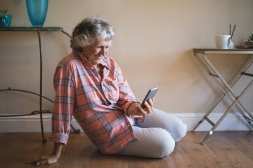 Senior woman using mobile phone while sitting on floor