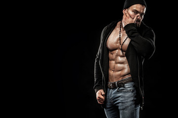 Handsome fit man posing wearing in jeans with tattoo. Sport and fashion concept isolated on black background.