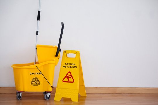 Yellow sign board with mop bucket on floor against wall