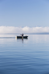 Man in a rowboat on lake Starnberg, the Alps and mount Zugspitze in early morning fog, Berg, Upper Bavaria, Germany