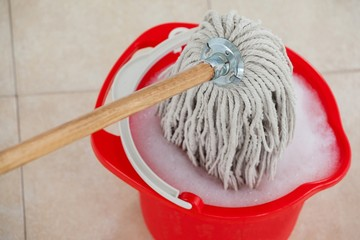 Bucket with foamy water and mopping the tile floor