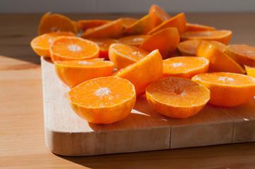 tangerines cut in half on a wooden board