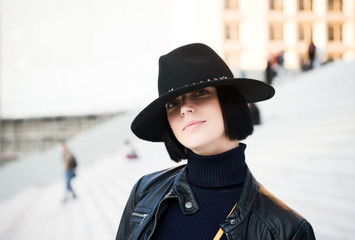 Woman in black hat and jacket pose on stairs