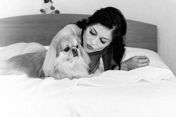 Beautiful brunette girl laying and cuddling her cute dog on bed with good mood at morning. Young woman is lying and sleeping with pekingese dog in bed.
