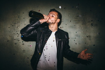 Man drinking champagne from the bottle