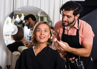 Man makeup specialist applying cosmetics for female