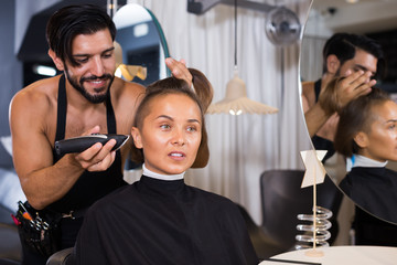 Adult man professional hairdresser cut woman's hair