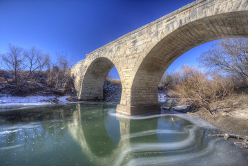 Clements Stone Arch Bridge over frozen stream, rural Kansas
