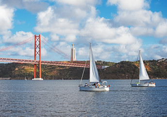 Bridge of 25th april with yachts in Lisbon.