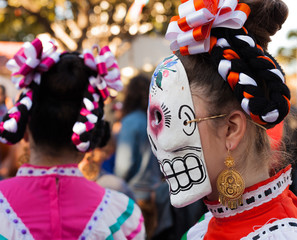 Profile of young woman wearing decorated skull mask and hair ribbons for Dia de Los Muertos/Day of the Dead celebration