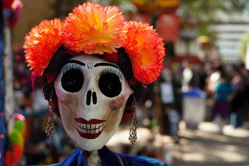 Skull painted and decorated with orange paper flowers and earrings/decorated skull for Dia de los Muertos, Day of the Dead