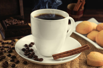 Cup of black coffee and grains of coffee with cinnamon sticks and cookies.