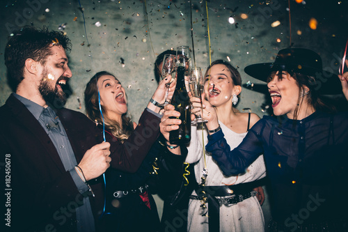 Group of happy friends drinking champagne and celebrating New Year ...