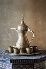 Turkish coffee set: Ottoman ornate coffee pot and small ornate cups on decorated tray, decorated Arabic style table and grunge background