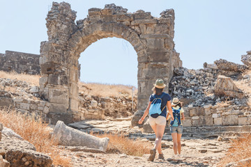 Two female friends of a tourist travels through the ancient ruined Greek city of Aspendos in Turkey