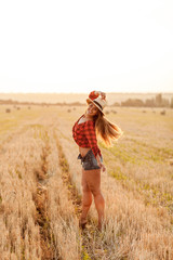 girl at sunset in a field in a red shirt