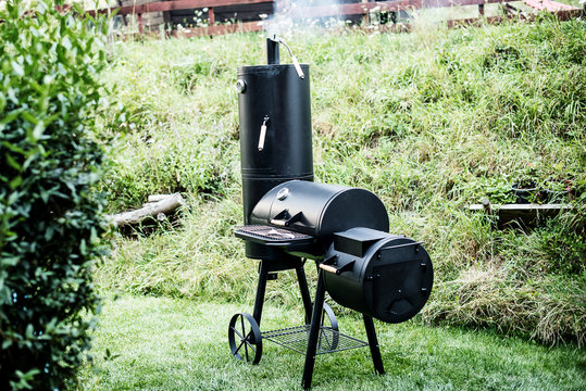 Black metal Locomotive grill with a pellet  smoker on green grass background