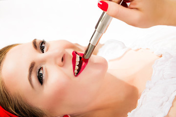 beautiful girl lies and paints lips with red lipstick