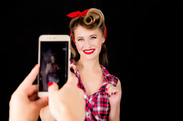 Somebody makes a photo on the phone of a girl in the style of pin-up