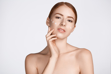 Attractive ginger woman is looking at camera with hands on white at studio