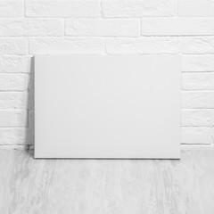 Mockup poster. White blank canvas leaning against a brick wall.
