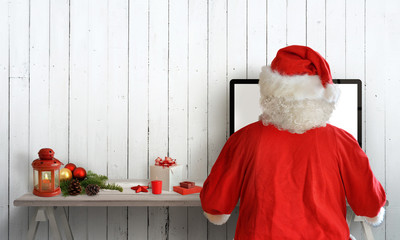 Santa Claus work on computer in his room. Free space on wall for text. Christmas decorations on desk.