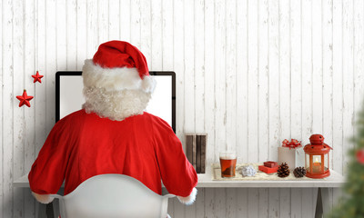 Santa Claus work on computer and send letters to kids. Christmas tree, gifts, and decorations beside. Free space for greeting text.