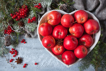 Red apples in a heart-shaped basket on a wooden background with Christmas tree branches and snow