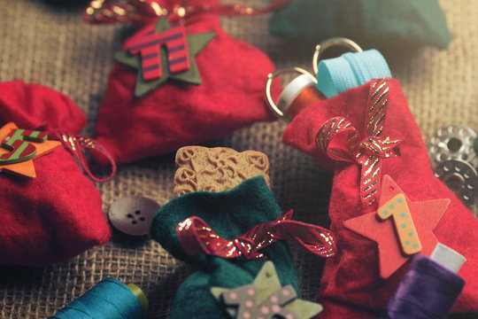 part view on traditional advent calendar with small fabric bags for individual filling atatched to a rough fabric decorated with sewing accessory - bright matte light mood