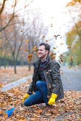 The man threw up the fallen leaves in the autumn park.
