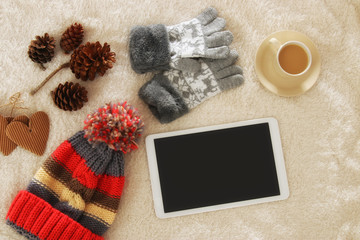Cup of coffee next to tablet device with empty screen over cozy and warm fur carpet. Top view.