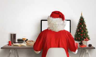 Santa Claus work on his computer. Christmas tree and gifts beside. Canta work desk with books, map, rope. Free space for text on white wall.
