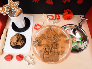 Making Christmas gingerbread cookies. Raw dough and red cookie cutters in toy kitchen with stove and sink