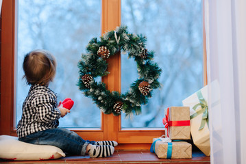 Charming child sits on before window decorated with Christmas wr