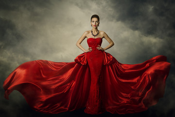 Fashion Model Art Dress, Elegant Woman Standing in Red Retro Gown, Silk Fabric Fluttering over Storm Sky Background