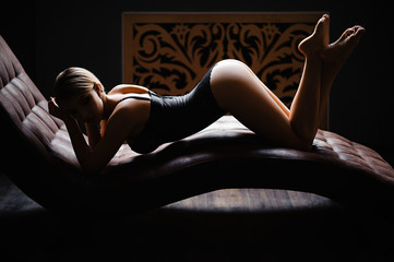 Sexy model with a perfect figure posing in bodysuit on the couch