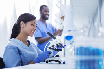 Professional female researcher. Nice happy positive woman sitting in front of the microscope and smiling while enjoying her job