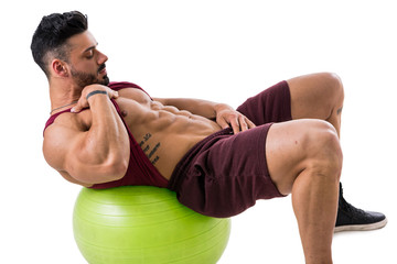 Attractive bodybuiler man exercising abs on an exercise ball in studio shot, isolatedo on white. Tattoo says Winning is not about not falling, but about not staying down