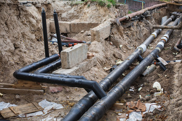 Water pipes with insulation lie on the ground. Construction works.