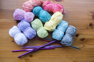 Colourful yarn bundles with crochet needles, taken on a wooden background