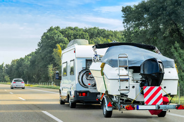 Caravan and trailer for motor boats on road in Switzerland