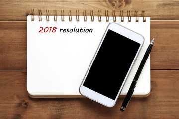 2018 resolution on blank notebook paper and smart phone on wood background, new yaer business and technology concept, mock up