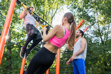 Low-angle view of an athletic young woman doing bicep curls with a suspension trainer during functional workout, with her friends in a modern outdoor fitness park