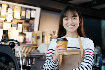 Young asia woman barista holding a diaposable coffee cup with smiling face at cafe counter background, small business owner, food and drink industry