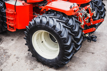 Big black rubber tire wheels of modern red tractor or combine or harvester